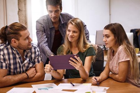 Team di pianificazione strategica in un brain storming meeting con una vivace discussione a un tavolo da conferenza con un tablet pc dall'aspetto positivo