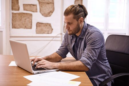Young businessman typing on his laptop while looking intently at what he is typing, sitting in an office chair with his hair tied back Stock Photo