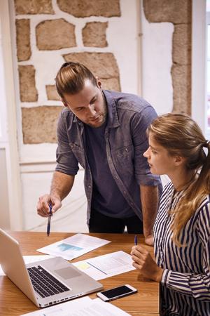 プロのビジネスの男性ノート パソコンを見ながら、businesslady で何かを議論する彼の手のペンと共有しています。