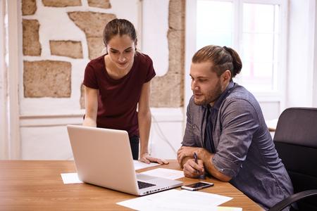 それら両方は彼の前に机の上ノート パソコンを見てのように彼の隣に立っている間若い男に指示する若い女性