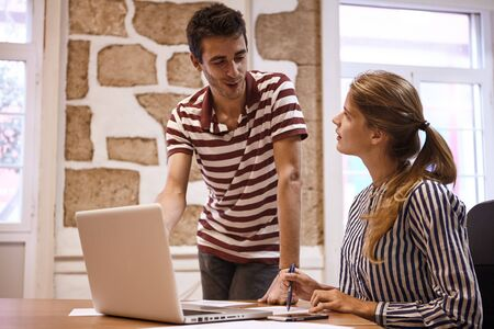 Young business woman pointing at her notes while looking at business man standing next to her discussing something with her