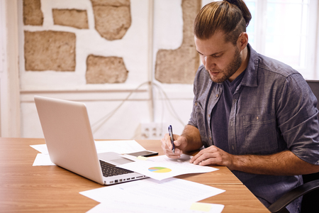 Businessman with tied back hair sitting at his desk with a laptop reading a chart in front of him with a pen in his hand Stock Photo