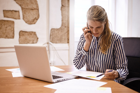 Young business woman discussing a chart with someone on the phone while pointing at it with a pen in her left hand