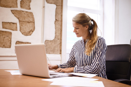 Professional young woman preparing for meeting making notes from her laptop while wearing a striped formal blouse and her hair tied up
