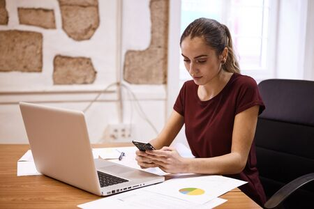 Pretty young business woman looking at her cell phone with her laptop open in front of her and some pie charts on her desk Stock Photo
