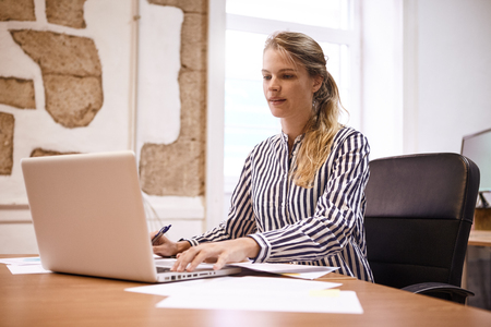 Professional young business woman looking at her laptop with a pen in one hand and scrolling with her other hand looking at the pc Stock Photo