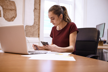 Young business woman sitting at her desk, making notes while holding her cell phone in one hand and a pen in the other hand