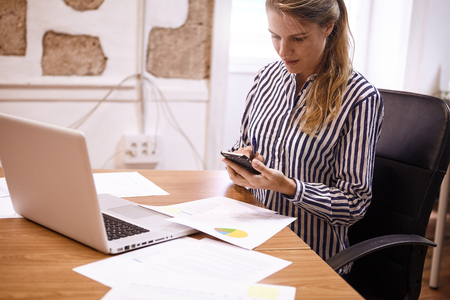 Young millenial business woman with her cellphone sitting at her desk with a pie chart and laptop in front of her Stock Photo