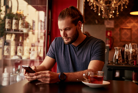 Professional young man sitting in a bar texting on his cell phone with a fridge behind him and a cup of tea on the table Stock Photo