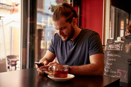 specials: Smiling young man reading a cell phone message while sitting in a pub with a cup of tea on the table and a fridge behind Stock Photo