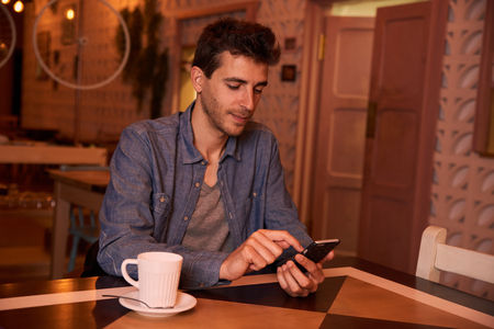 Thinking young man wearing a denim shirt in a restaurant typing on his cellphone with a mug of coffee to his right