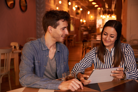 intimately: Intimately smiling millenial couple sitting at a table in a restaurant with toothy smiles while looking at a tablet she is holding Stock Photo