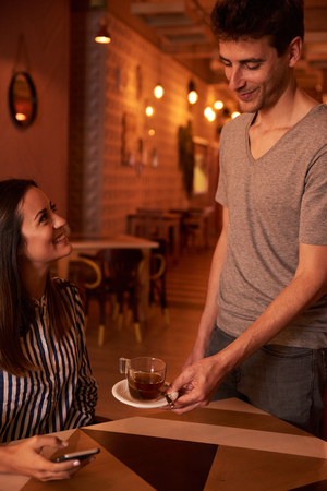 Young male waitron serving a cup of tea to a lovely young lady in a restaurant while she looks at him with a toothy smile