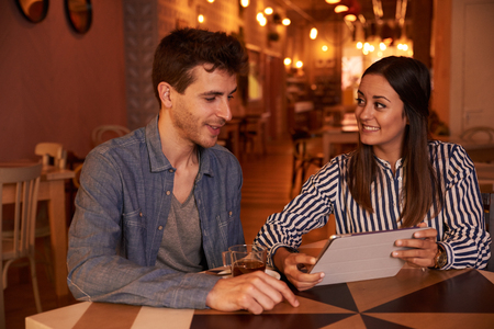 intimately: Intimately smiling millenial couple sitting at a table in a restaurant with toothy smiles while she is looking at him expectantly Stock Photo
