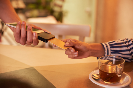 Male hand holding credit card paying machine out to female hand with gold credit card with half a cup of tea on the table