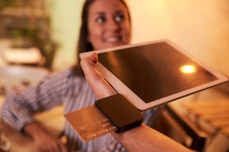 looking away from camera: Out of focus millenial woman paying her bill with a gold credit card and male hand holding payment device in his left hand Stock Photo