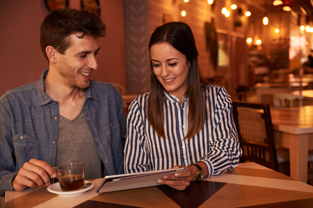 intimately: Millenial couple sitting close together in a restaurant while sharing intimately on a tablet she is holding for them both to see