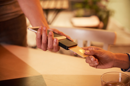 Male hand with credit card paying machine and female hand with gold credit card with half a cup of tea on the table