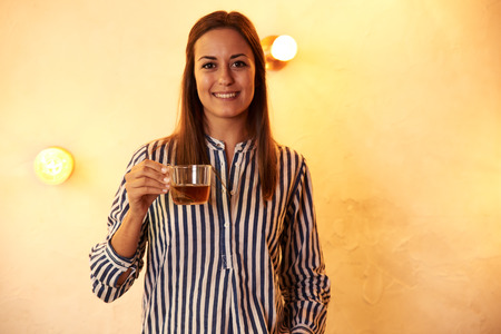 Woman looking and smiling at camera while holding a cup of tea in her right hand as she stands in front of brightly lit wall