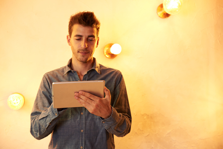 Goodlooking young male texting on his tablet with a knowing smile while standing in front of a brightly lit wall