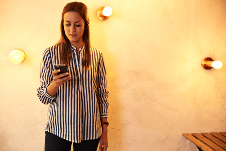Lovely young woman texting a message on her cell phone while standing against a brightly lit wall wearing a striped shirt and black pants