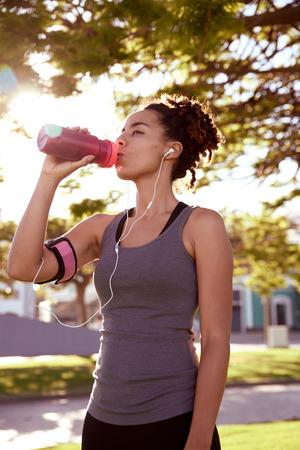 フィット若い訓練女性イヤホンで彼女の音楽プレーヤーを聴きながらピンクの水筒からいくつかの水を飲む