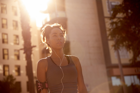 Fit female runner with earphones and a music player looking far ahead of her with bright reflective sunshine and buildings behind her