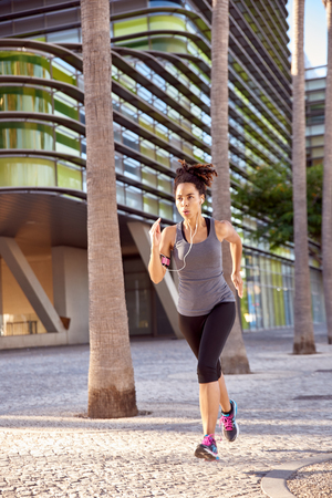 Fit woman in training is running with concentration while listening to music on her player with earphones