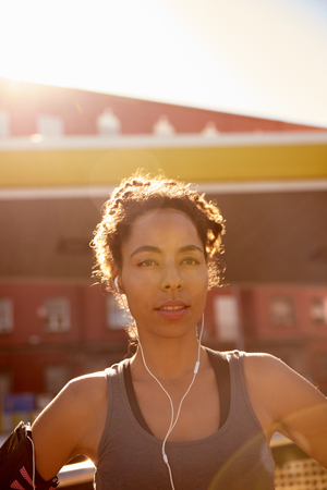 Woman with earphones listening to music while looking past the camera with glaring sunshine and buildings behind her Stock Photo