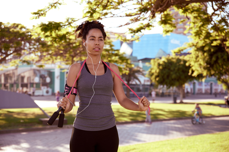 Fit young woman resting with her skipping rope around her neck while listening to music on her music player with earphones