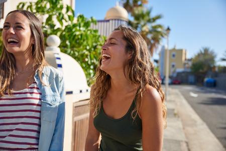 Twee mooie jonge meiden komen uit voor een wandeling onbeheersbaar lachen terwijl ze buiten genieten in de zon Stockfoto
