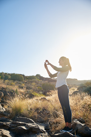 Lovely young girl wearing jeggings and a t-shirt taking a photo with her cellphone while standing on a big rock in bright reflective sun