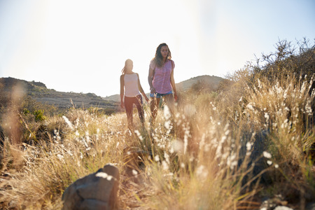 Two healthy young ladies hiking on a grassy hill wearing casual clothing with their arms beside them in the afternoon sun Stock Photo