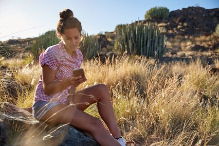 Pretty young girl sitting on a rock on a grassy hillside looking at her cellphone while wearing jean shorts and a buttoned shirt