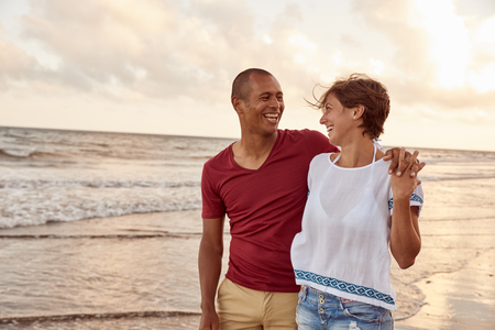 Joyfully laughing embracing couple in love looking at each other on the beach shore while enjoying the breaking waves around their feet Stock Photo