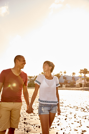 Couple with eyes for only each other holding hands while taking a lovely walk on the empty beach with bright white sky behind them Stock Photo
