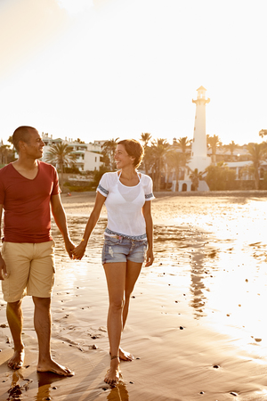 Loving adult couple walking barefoot on the beach while looking at each other lovingly with a light tower behind them and bright reflective white sky