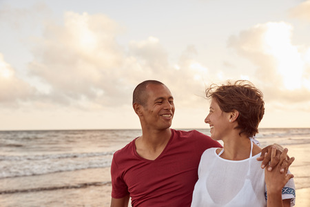 Joyfully laughing embracing couple in love looking at each other on the beach shore while enjoying the breaking waves of the sea behind them Stock Photo