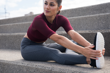 Pretty young female stretching on stairs wearing modern sports clothes with hair tied back