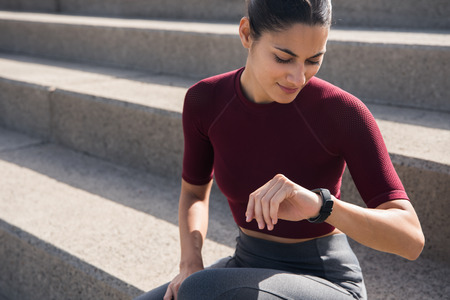 Young brunette girl looking at watch while sitting on stairs in fitness clothing Stock Photo