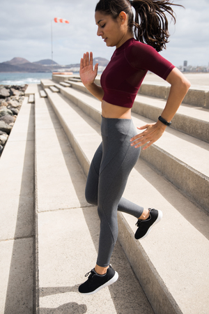 Attractive fit female running down stairs in a midriff sport shirt with grey tights