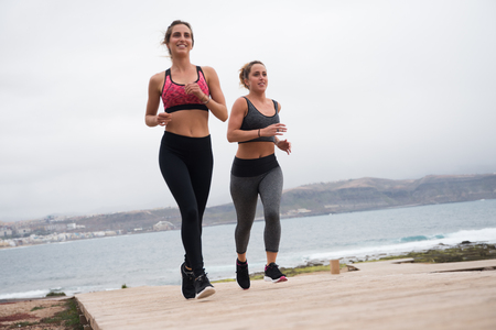 Happy women running on the boarwalk looking good in fitness tights and crop tops with hair tied back