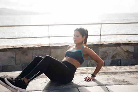 A woman with a sporty body exersising outside in black tights, grey crop top and black sneakers