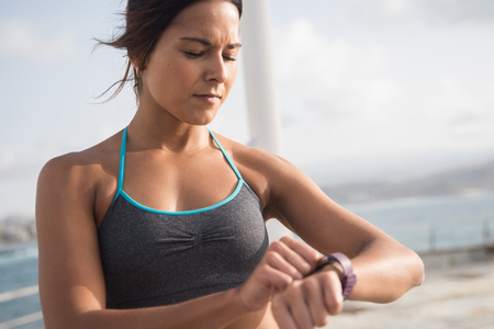 Upper half of young brunette in fitness top looking at her smartwatch with the sun shining on her