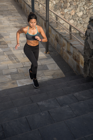 A fit young woman running up grey stairs in her black tights and grey tank top with the sun on her skin