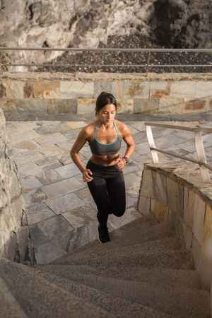 A fit young woman runs up grey stairs with the sun on her skin and wearing black tights and a tank top