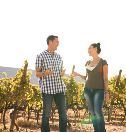 Couple spending time together in nature on a beautiful sunny day in the vineyards wearing casual clothing