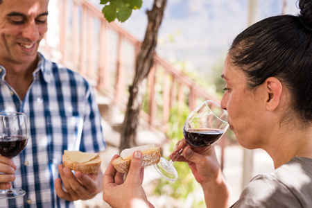 Couple eating bread and drinking wine at a vineyard he is smiling and they are both looking at the food