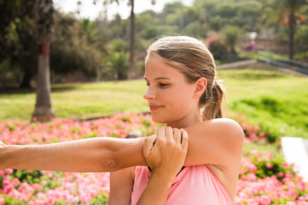 Young girl doing stretching exercises in the park holding her arm up and looking down the length of her arm