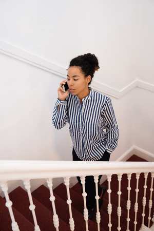 Young woman walking up a flight of stairs wearing a stripped button down top and black trousers talking on a cell phone